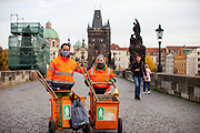 Pepa (left) and Hana, both working for the city of Prague to keep the city clean posing for a portrait with face masks on Charles Bridge in Prague. As of 21st of October 2020 people have to wear face masks outside and inside.