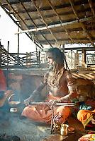A Hindu holy man playing chimta and chanting at the ghats in Varanasi, Uttar Pradesh, India