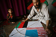 Noor Agha, 52, measures a bamboo stick for a kite ordered by an American client (with both Afghan and American flags) in the house as his daughter, Sobra, 6 or 7, looks on in their house, Kabul, Afghanistan, Monday, July, 9, 2007. Noor Agha is a renowned kite maker who made kites for the movie makers of the best-selling novel, The Kite Runner, which will be distributed by Dreamworks and Paramount Vantage in Nov. this year. Noor Agha's wives, using their special glue, help him produce enough kites to please the clients' needs.