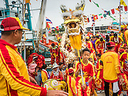 "23 JUNE 2015 - MAHACHAI, SAMUT SAKHON, THAILAND: Chinese dragon dancers get off a fishing boat during the procession for the City Pillar Shrine in Mahachai. The Chaopho Lak Mueang Procession (City Pillar Shrine Procession) is a religious festival that takes place in June in front of city hall in Mahachai. The ""Chaopho Lak Mueang"" is  placed on a fishing boat and taken across the Tha Chin River from Talat Maha Chai to Tha Chalom in the area of Wat Suwannaram and then paraded through the community before returning to the temple in Mahachai.   PHOTO BY JACK KURTZ"
