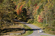 Fall foliage in mid October on the Blue Ridge Parkway. The popular Humpback Rocks Trail (2 miles round trip with 700 feet gain) starts here at Milepost 6 of the Blue Ridge Parkway, in Virginia, in the Blue Ridge Mountains (a subset of the Appalachian Mountains), USA. On left is the log fence of Humpback Rocks Mountain Farm, a restored 1890s farmstead open to the public at Milepost 5.8. In summer, costumed interpreters demonstrate 1890s southern Appalachian mountain life. European settlers of the Appalachian Mountains forged a living from abundant native materials: hickory, chestnut, and oak trees provided nuts for food, logs for building, and tannin for curing hides; and the rocks were used as foundations, chimneys and stone fences. This farm was originally a Land Grant tract dispensed by the Commonwealth of Virginia to induce pioneers to settle; and later it became known as the William J. Carter Farm. The scenic 469-mile Blue Ridge Parkway connects Shenandoah National Park, Virginia, with the Great Smoky Mountains National Park in North Carolina, following ridge crestlines and the Appalachian Trail.