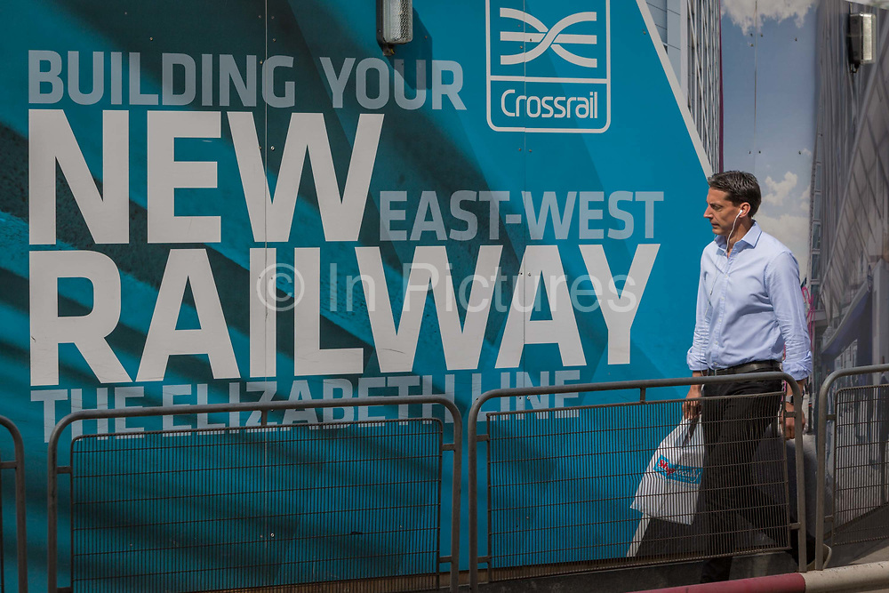 Londoners and commuters walk past the billboards promoting Crossrails new Queen Elizabeth rail line, the capitals newest  on 3rd September 2018, on Moorgate in London, England. Crossrails Elizabeth Line is a 118-kilometre 73-mile railway line under development in London and the home counties of Berkshire, Buckinghamshire and Essex, England. Crossrail is the biggest construction project in Europe and is one of the largest single infrastructure investments ever undertaken in the UK - a£15bn transport project that was due to open in December 2018 but now delayed to autumn 2019.