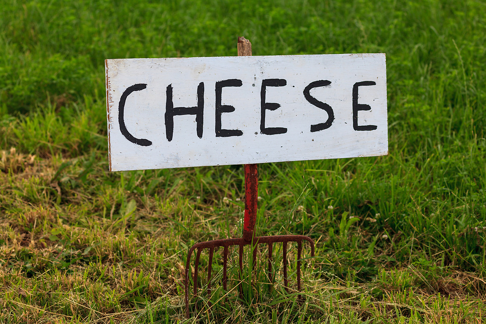 A sign offering cheese for sale on an Amish farm in Lancaster County, fashioned out of a pitchfork.