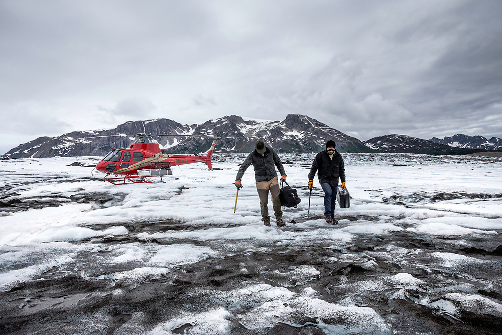 Two men pack in their gear to check purity samples of glacial water during the summer months in northern Alaska.