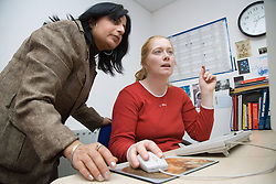 Young woman in a computer training session with teacher,