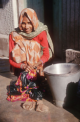 Woman crouching in street washing clothes smiling,