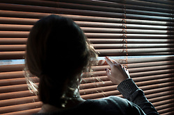 A woman looks out a window through a blind. Picture posed by model - model release available.