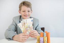 Boy with coin rolls and paper money, smiling, portrait
