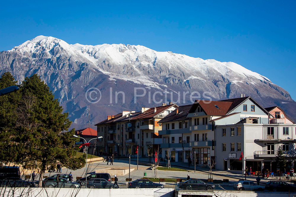 A street scene in Bajram Curri with snow topped mountain in the Valbona Valley National Park behind on the 12th of December 2018, Albania. Bajram Curri is a town located in northern Albania, very close to the border with Kosovo, in a remote, mostly mountainous region. The town is named after Bajram Curri, a national hero who fought for ethnic Albanians, first against the Ottoman Empire and later against the Albanian government.