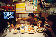 Saturday night meal at the Ukita house, always accompanied by the fifth member of the family: the television. Japan. Material World Project. The Ukita family lives in a 1421 square foot wooden frame house in a suburb northwest of Tokyo called Kodaira City.