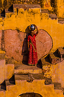 A local woman going to fetch water in Panna Meena Ka Kund step well, (baori), Amer (near Jaipur), Rajasthan, India.