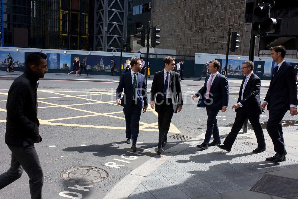 Old colleagues greet each other in the City of London as an outsider looks on. Some of the men have recognised each other while with others as they head over Bishopsgate in the capital's financial heart. On the left is an outsider, a stranger with darker skin than the group of young professionals wearing suits. He makes his own way in the opposite direction, looking at the men with hands in pockets.