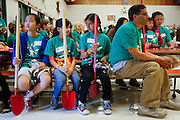 From left to right, Davalyn Le, 9, Saili Karkare, 9, Apurva Pendse, 9, and Ashutosh Pendse listen to the welcoming announcements during Comcast Cares Day at Curtner Elementary School in Milpitas, California, on April 27, 2013. (Stan Olszewski/SOSKIphoto)