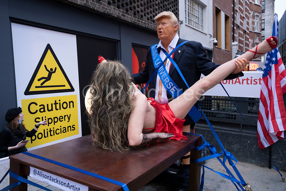 (EDITORS NOTE: Image contains graphic material) Explicit art installation 'Donald Trump and Miss Universe' by English artist Alison Jackson on the back of a truck in Soho on 30th October 2020 in London, United Kingdom. The artwork shows Donald Trump with American flags, wearing a Miss Universe sash having intercourse with a woman in a red dress balanced on a table. Jackson is a contemporary BAFTA and multi award winning artist who explores the cult of celebrity and is known in particular for her photographs of lookalike celebrities.
