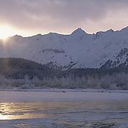 Alaska, sun setting behind the Chilakeat River and Chilakeat Mountain Range. Winter.