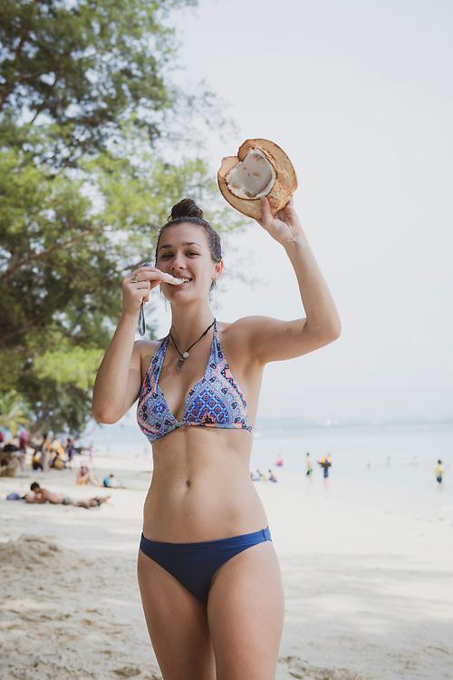 Gabrielle, traveling in Borneo, eats a fresh green coconut at the beach on Manukan Island near Kota Kinabalau, Sabah, Malaysia.