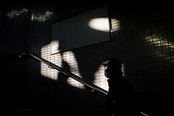 A man walks up stairs of neighborhood subway in Kamagasaki, Japan.