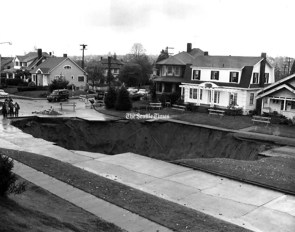 Barricades block sidewalks of homes along the Ravenna Avenue sinkhole the day after it appeared. (Seattle Times Archive, 1957)