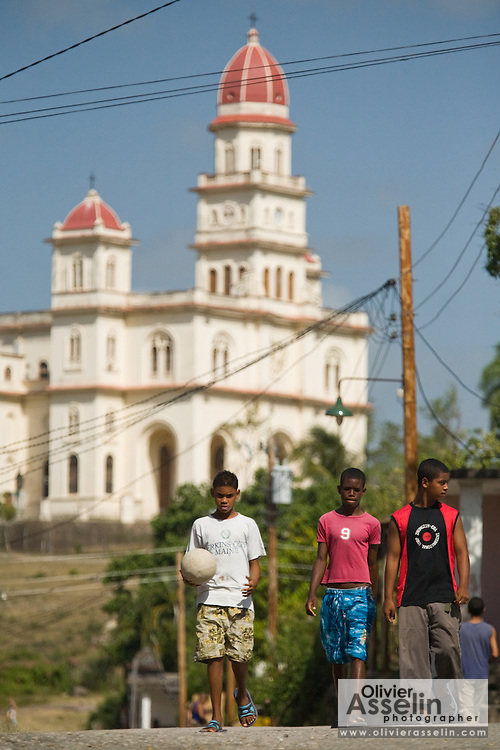 Boys walk down a street near the basilica of El Cobre, Cuba on Wednesday July 9, 2008.