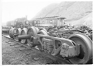 """Durango yard with #464 stored for rebuilding with a derelict passenger car.  Foreground of truck and wheelsets, scrap pile beyond.<br /> D&RGW  Durango, CO  <br /> In book """"Durango: Always a Railroad Town (1st ed.)"""" page 175"""