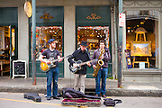 Jazz musicians saxophonist and guitarist in live busking performance on street corner in French Quarter, New Orleans, USA