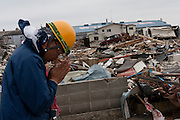A Peace Boat volunteer prays for the visctims of the tsunami during clean up operations in Ishinomaki that was bad affected by the earthquake and tsunami that struck on March 11th.  Ishinomaki, Miyagi, Japan. Friday May 6th 2011