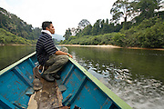 Aslan, an Orang Asli guide, rides at the bow of a jungle boat on the Endau River during a trip to Endau-Rompin National Park, Malaysia.