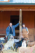 Vern and Gianaclis Caldwell with the guard dog, Sophie, in the barn with the Nigerian Dwarf Goats.