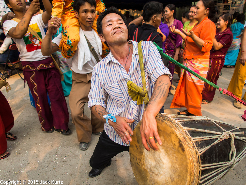 """05 APRIL 2015 - CHIANG MAI, CHIANG MAI, THAILAND: A man plays a traditional Shan drum during a parade of novice monks on the second day of the three day long Poi Song Long Festival in Chiang Mai. The Poi Sang Long Festival (also called Poy Sang Long) is an ordination ceremony for Tai (also and commonly called Shan, though they prefer Tai) boys in the Shan State of Myanmar (Burma) and in Shan communities in western Thailand. Most Tai boys go into the monastery as novice monks at some point between the ages of seven and fourteen. This year seven boys were ordained at the Poi Sang Long ceremony at Wat Pa Pao in Chiang Mai. Poy Song Long is Tai (Shan) for """"Festival of the Jewel (or Crystal) Sons.    PHOTO BY JACK KURTZ"""