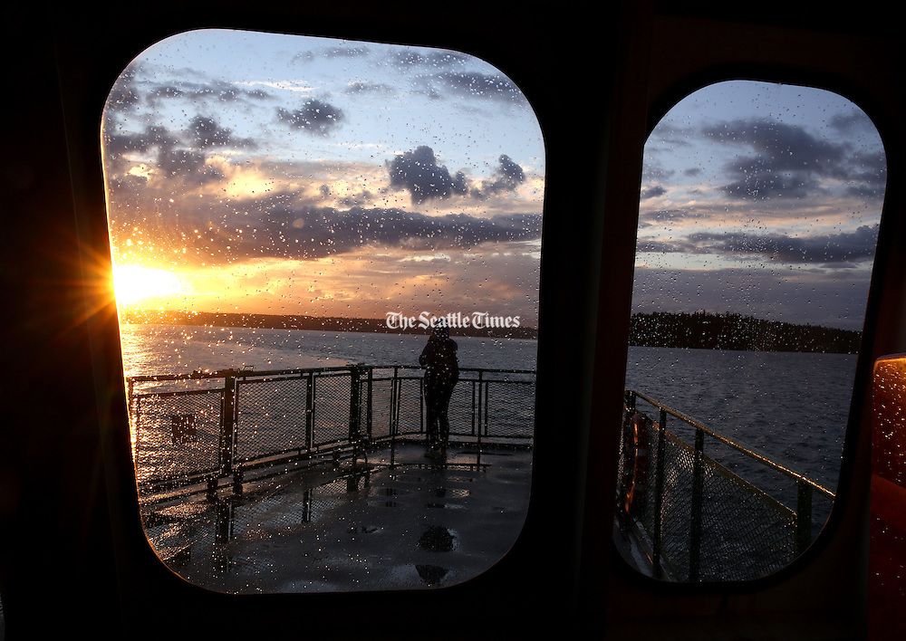 A ferry passenger watches the sunset while riding on the ferry from Southworth to Fauntleroy during a stormy September evening. (Erika Schultz / The Seattle Times)
