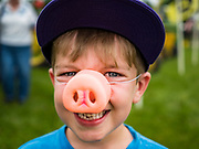 26 JUNE 2019 - CENTRAL CITY, IOWA: A boy wears the pig nose he won by cheering for the winning pig in pig racing at the Linn County Fair. Summer is county fair season in Iowa. Most of Iowa's 99 counties host their county fairs before the Iowa State Fair, August 8-18 this year. The Linn County Fair runs June 26 - 30. The first county fair in Linn County was in 1855. The fair provides opportunities for 4-H members, FFA members and the youth of Linn County to showcase their accomplishments and talents and provide activities, entertainment and learning opportunities to the diverse citizens of Linn County and guests.       <br /> PHOTO BY JACK KURTZ
