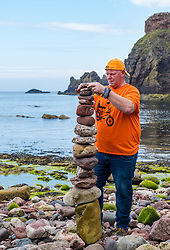 Dunbar, East Lothian, Scotland, United Kingdom 10 July 2021. European Stone Stacking Championship: The first day of the event, which is part of the Edinburgh Science Festival.  Pictured: Dicey Turnbull, from Bonnyrigg, competes in the most stones stacked in half an hour competition. The record is 42.<br /> Sally Anderson | EdinburghElitemedia.co.uk