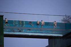 © Licensed to London News Pictures. 31/05/2021. London, UK. Members of the public are see in the suspended swimming pool on the sunny day during bank holiday in Embassy Gardens, central London. Photo credit: Marcin Nowak/LNP