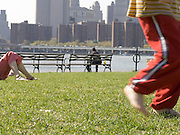 Public park NYC child running mother laying in the grass and person on bench.