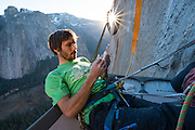 Kevin Jorgeson on the portaledge taking a survey of the skin on his finger tips before launching off on pitch 14, 5.14d, on the Dawn Wall of El Capitan in Yosemite National  Park. This was on December 22nd, 2014, just weeks before his historic first ascent of the route with partner Tommy Caldwell.