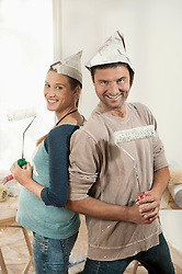 Couple holding paint rollers and smiling, Bavaria, Germany