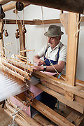 Weber arbeitet an Webstuhl, Webereimuseum Breitenberg, altes Bauernhaus, Bayerischer Wald, Bayern, Deutschland | weaver working on loom, weaving museum near Breitenberg, Bavarian Forest, Bavaria, Germany