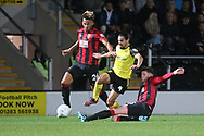 Burton Albion defender Ryan Edwards (4) is tackled by Bournemouth's Lloyd Kelly (26)  and Bournemouth's Jack Simpson (25) during the EFL Cup match between Burton Albion and Bournemouth at the Pirelli Stadium, Burton upon Trent, England on 25 September 2019.