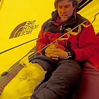 BAFFIN ISLAND, Nunavut, Canada. Alex Lowe (MR) broods about injured knee during remote Great Sail Peak expedition.