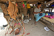 A mother sews, sheltered from the scorching sun, in the shadow of her pile dwelling next to her sleeping son. A poster of Aung San Suu Kyi and her father,  General Aung San, overlooks the scene..Nyaung U, Myanmar. 2012