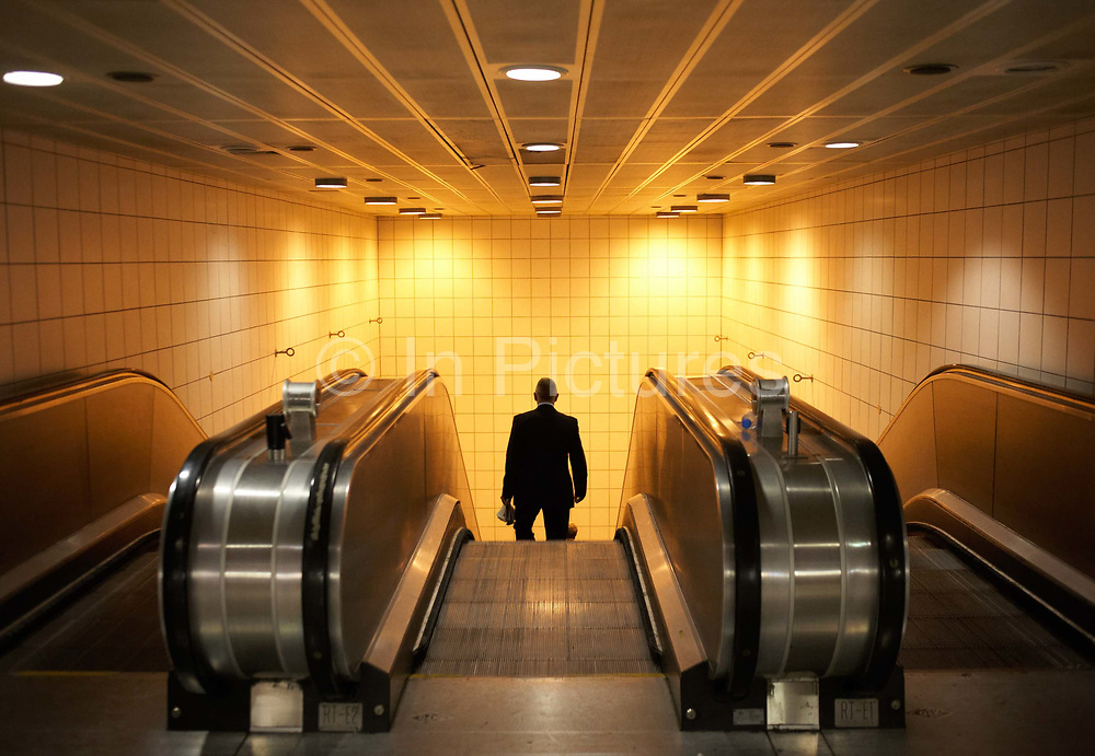 A male commuter disappears underground after a rail journey terminated at the London Bridge mainline station. Travelling downwards into the London Underground tube system, the man seen as a generic silhouette is seen only from the upper legs and moves against the orange light from the escalator well wall. The polished machinery is in the foreground and the floor is spotlessley clean. London Bridge station is one of 18 railway stations managed by Network Rail and is a major transport terminus and interchange for central London and serves over 42 million people a year. The tube station serves the Jubilee Line and the Bank branch of the Northern Line.