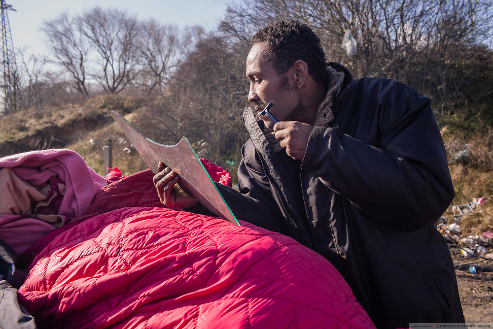 Calais, France, 27 feb 2015, Situation of the migrants in Calais, living in jungles. A refugee from Sudan is shaving in the reflection of a piece of mirror.