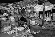 Padre e hija dentro del campamento de migrantes en Matamoros, Tamaulipas. El padre le ayudar a su hija a hacer su tarea. Matamoros, Tamaulipas. Fotografo César Rodríguez.