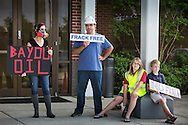 """May 12, Mandeville  LA, Hunter Montgomery, founder of the facebook group  """"Frack Free St. Tammany""""  with his chlidren Grady and Emma  and Stephanie Houston Grey, founder of Facebook group """"Keep Your Fracking Drills"""" hold protest signs up in front of the Castine Center in Mandeville before an educational meeting hosted by St. Tammany Parish Councilman Jake Groby.  Environmental scientist  Wilma Subra and John Barry spoke at the meeting.  Helis Oil & Gas, the company who wants to frack in the area did not send a representative to the meeting though they were invited and expected to be in attendance."""
