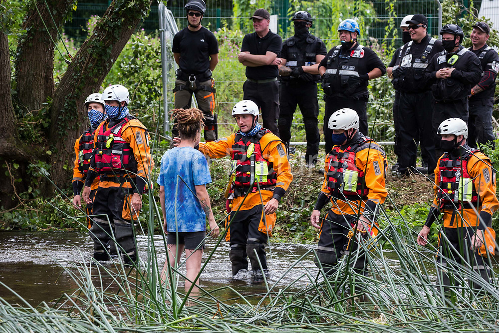 Police officers from Hampshire Police Marine Support Unit ask a female environmental activist from HS2 Rebellion to move away from an ancient alder tree which she had been trying to protect from destruction during works for the HS2 high-speed rail link on 24th July 2020 in Denham, United Kingdom. A large security operation involving officers from the Metropolitan Police, Thames Valley Police, City of London Police and Hampshire Police as well as the National Eviction Team ensured the removal of the tree by HS2 despite the protests by activists.
