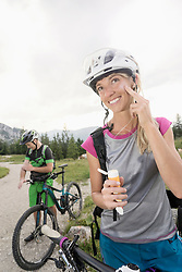 Mountain bikers applying sun cream, Kampenwand, Bavaria, Germany