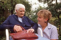 Elderly woman sitting in garden with carer,