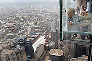 Anna Kane, 5, of Alton, Illinois looks out over the city from The Ledge, a series of glass bays that extend out from the 103rd floor Skydeck of the Sears Tower in Chicago on July 1, 2009. The Ledge, which opens to the public on July 2, gives visitors a uniquie view of Chicago from the 4-foot glass extensions including the view 1,353 feet straight down. (UPI)