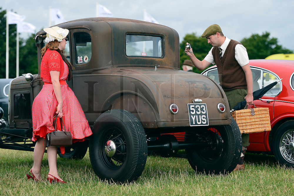 © Licensed to London News Pictures. 15/09/2013. Chichester, UK People enjoy the atmosphere at the last day of 2013 Goodwood Revival. The event recreates the glorious days of motor racing and participants are encouraged to dress in period dress. The revival is the only event of its kind to be staged entirely in the nostalgic time capsule of the 1940s, 50s and 60s Photo credit : Stephen Simpson/LNP.