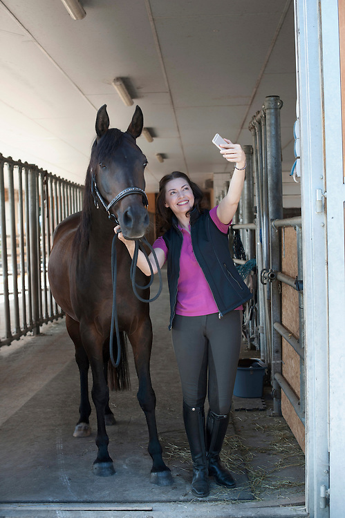 Mature woman taking a selfie with her brown horse in stable and smiling, Bavaria, Germany